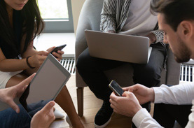 Group of four with devices huddled and brainstorming