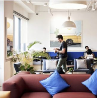Private office with people spread out and nice couch in foreground