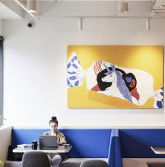 Blue couches with yellow painting and woman sitting studying