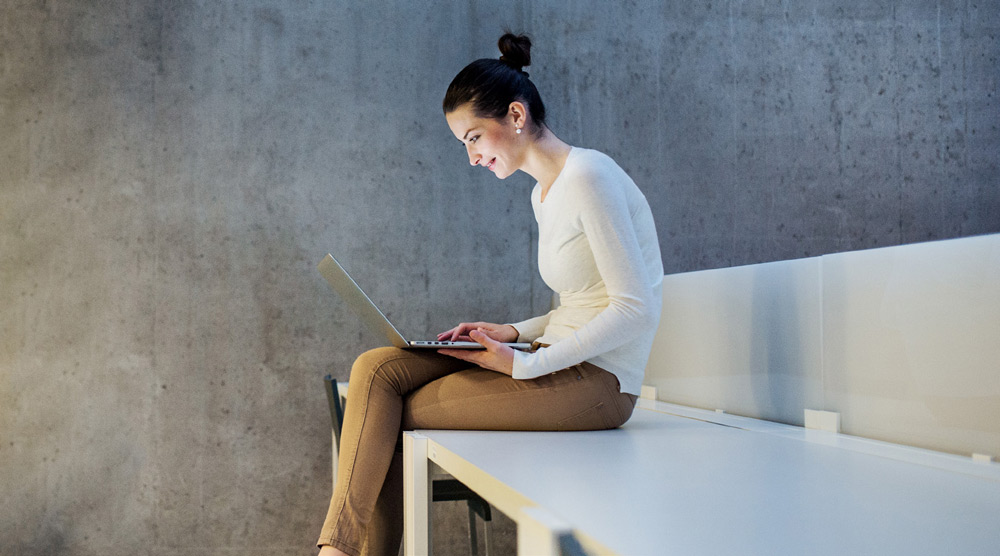 Woman sitting on white bench working on her laptop